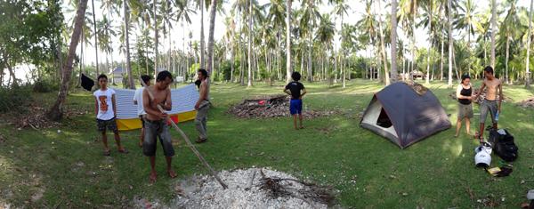 mendirikan tenda di kebun kelapa dekat pantai
