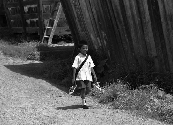 Hemat Sepatu - anak lelaki pulang sekolah menjinjing sepatu (lokasi: Lempur Mudik)
