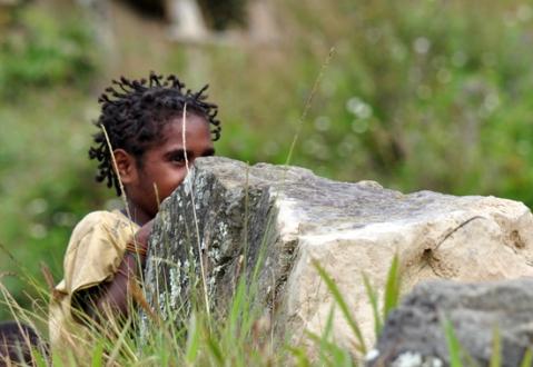 gadis cilik bersembunyi di balik batu