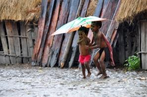 anak-anak berlarian di tengah hujan