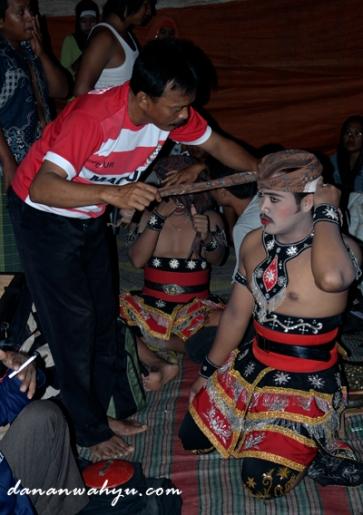 Pak Saleh membantu penari mengenakan ikat kepala