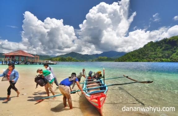 berlompatan turun dari perahu untuk merasakan lembutnya pasir