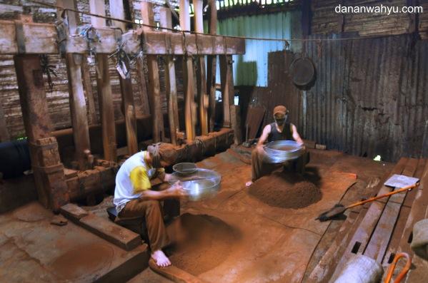 dua pekerja mengayak remah-remah kopi