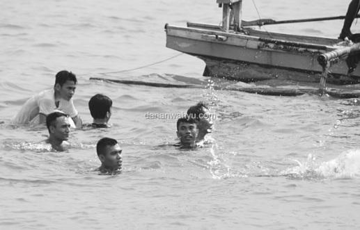 pria mencebur ke lautan melarungkan sesaji