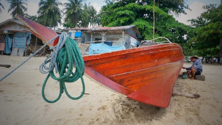 nelayan memperbaiki kapal di pantai Nongsa