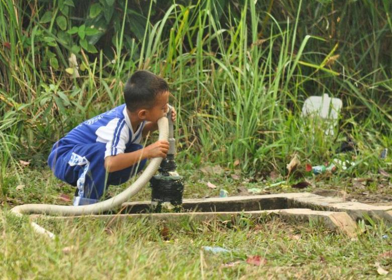 Minum sumber air bersih di samping sekolah