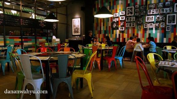 Kursi warna-warni menyemarakan ruangan didominasi warna hitam