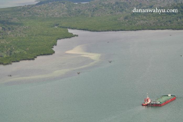 Saya penasaran dengan kapal kecil penarik tongkang bermanufer di selat antara pulau kecil.