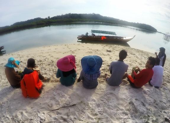 Nongkrong cantik di pantai pulau Rano sambil minum air kelapa muda