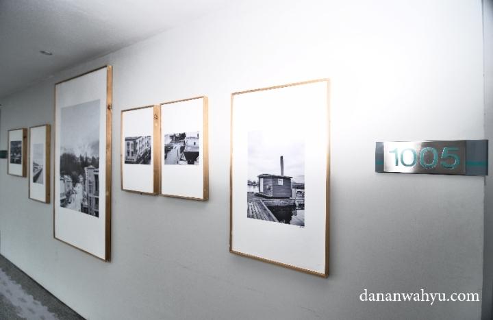 Foto hitam putih tergantung di sepanjang lorong kamar