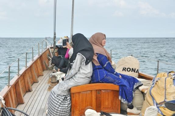 Dua gadis berpakaian Melayu berlayar untuk menyaksikan perlombaan yacht.