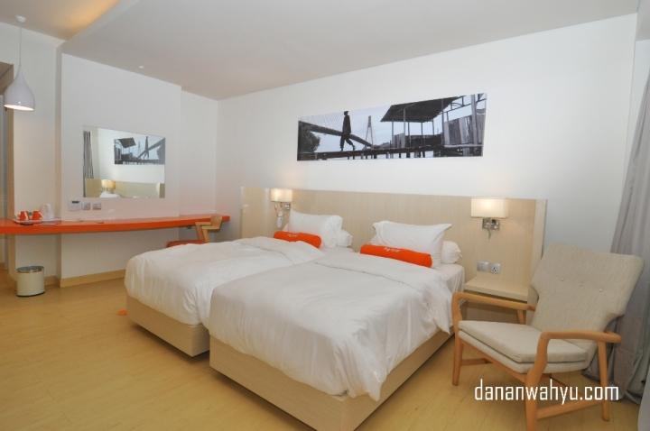 Desain interior kamar didominasi warna putih dengan oranye , krem dan hitam menjadi pemanis.