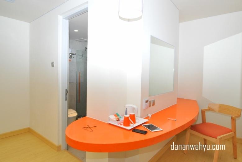 Meja oranye luas untuk menjembreng gadget dan meja kerja.